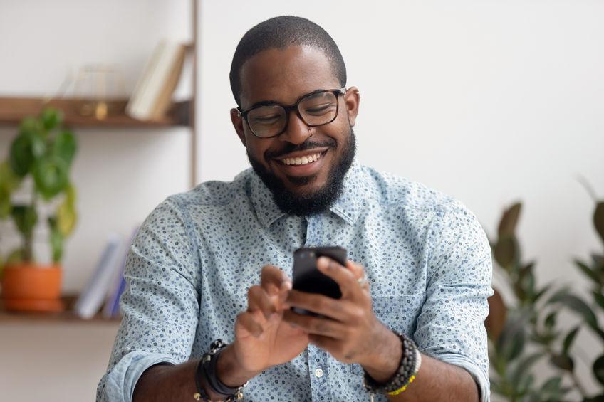 hombre feliz mirando celular