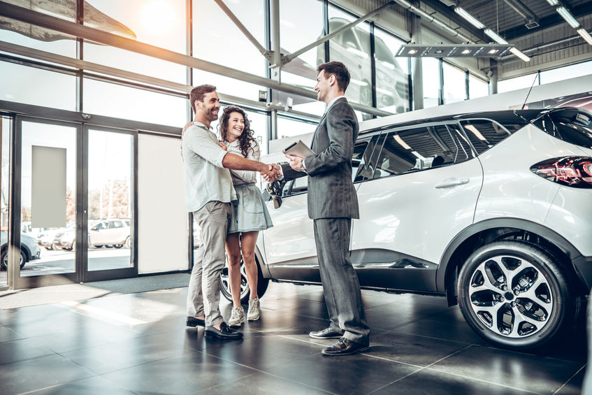 Young couple shaking hands with sales agent after a successful car buying.