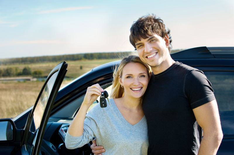 portrait of happy bautiful couple showing the keys standing near the car