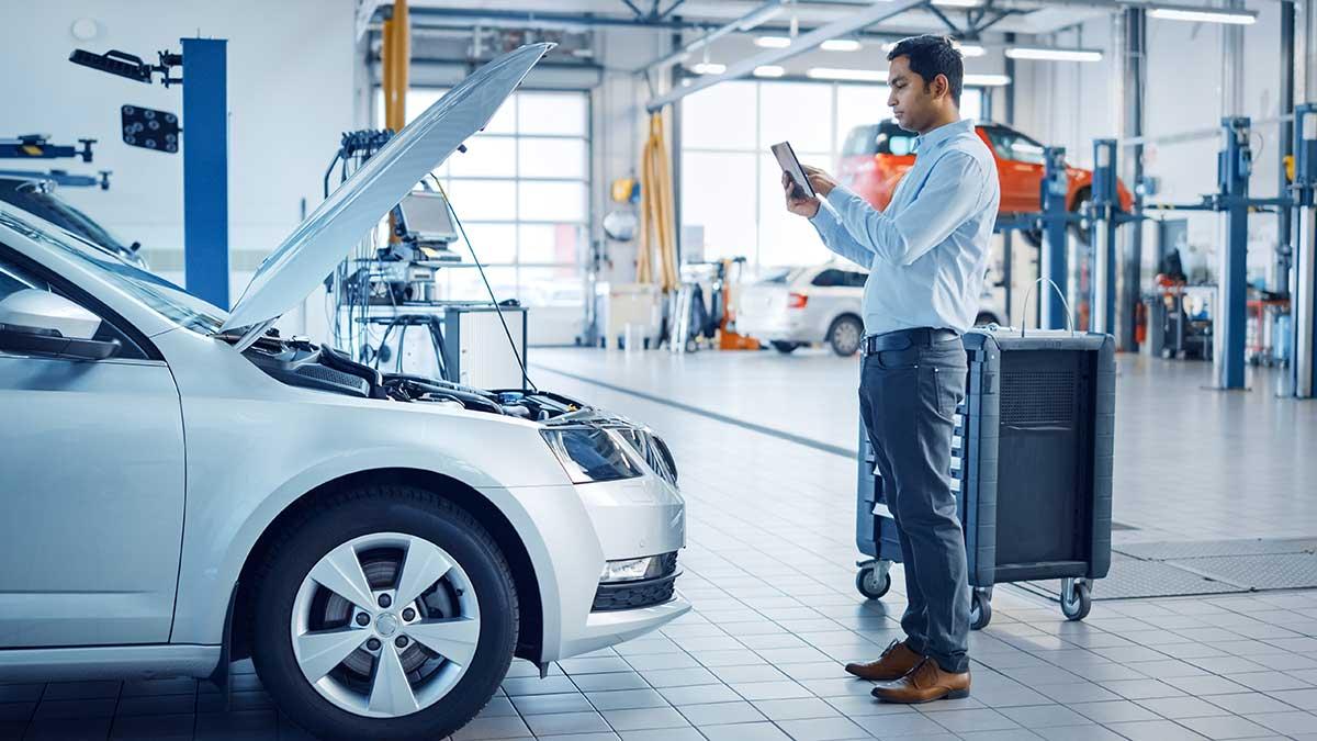 hombre inspeccionando coche con móvil